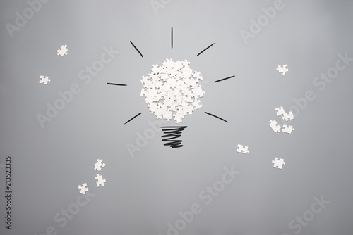 Foto  Scattered puzzle pieces forming a light bulb on a grey background