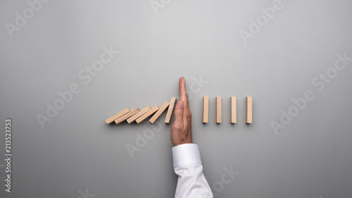 Foto Male hand in white shirt stopping falling dominos on gray desk