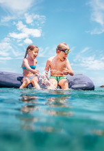 Two Childs, Sister And Brother, Have Fun When Swim On Inflatable Mattress In The Sea