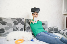 Beautiful Disabled Young Woman With Virtual Reality Goggles Sitting On Couch And Preparing For Playing Video Game.