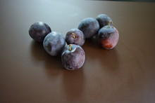 Fresh Ripped Plums On A Brown ...