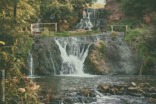 Wall Murals Ostrich Beautiful mountain rainforest waterfall with fast flowing water and rocks, long exposure. Natural seasonal travel outdoor background in hipster vintage style