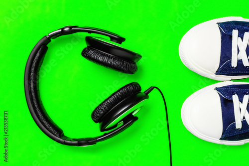 Láminas  A pair of new stylish sneakers and headphones on a green bright background