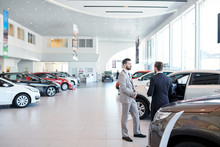 Professional Salesperson Selling New Cars In A Modern Auto Salon. Two Men Standing And Choosing A New Car