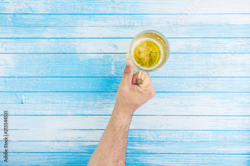 In de dag Bier / Cider Hand Holding Beer Mug Full Of Beer With Foam Top View On Blue White Woold Background