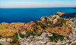 Aerial birds eye view drone photo of village Lindos, Rhodes island, Dodecanese, Greece. Sunset panorama with castle, Mediterranean coast and Saint Paul bay. Famous tourist destination in South Europe