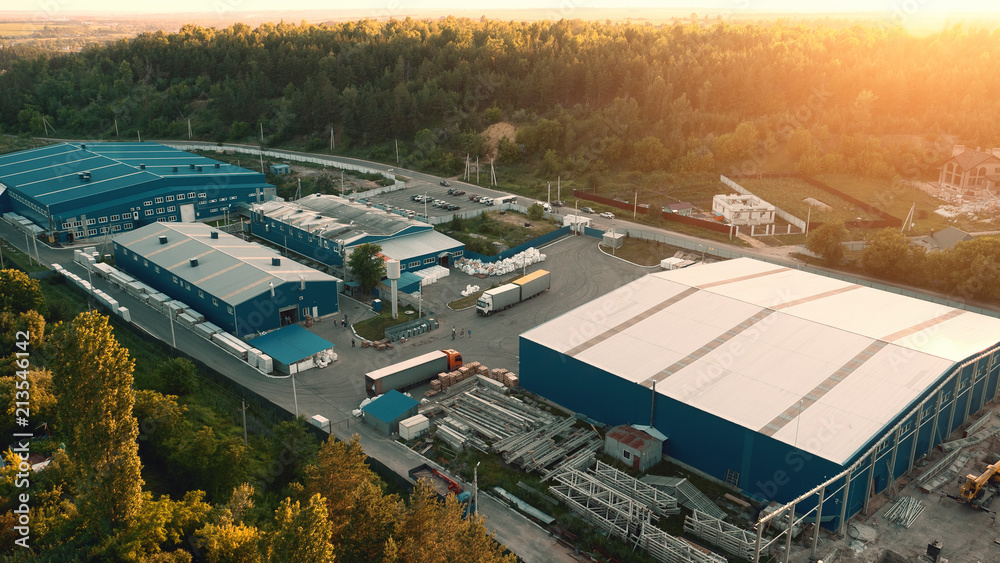 Fototapeta Aerial view of warehouse storages or industrial factory or logistics center from above. Aerial view of industrial buildings at sunset