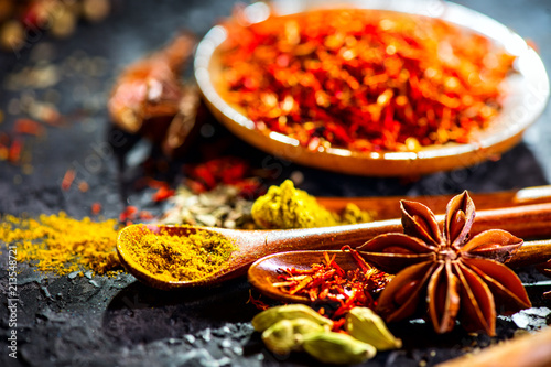 Deurstickers Aromatische Spices. Various Indian spices on black stone table. Spice and herbs on slate background. Cooking ingredients