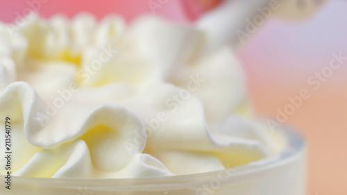 Fotografia  Swirls of whipped cream, macro closeup preparation for cake decorating