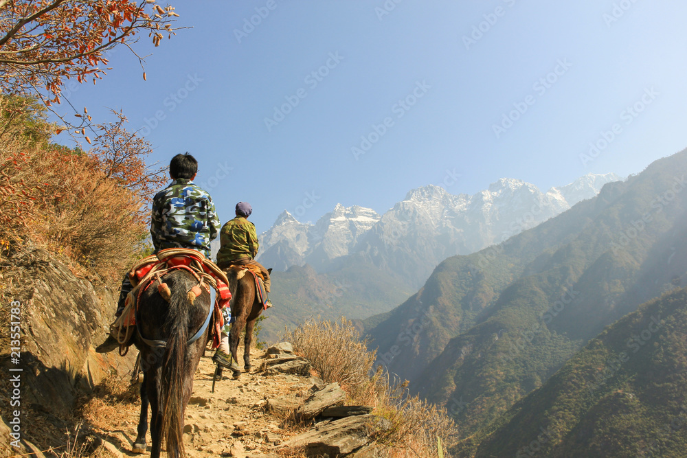 Fototapety, obrazy: Father and son riding donkeys on the path of the Tiger Leaping Gorge, Yunnan province, China. Dangerous cliff edge, hiking concepts