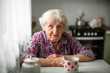 canvas print picture - An elderly russian woman sitting at the kitchen table.