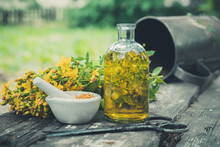 Hypericum - St Johns Wort Flowers, Oil Or Infusion Transparent Bottle, Mortar On Wooden Table.