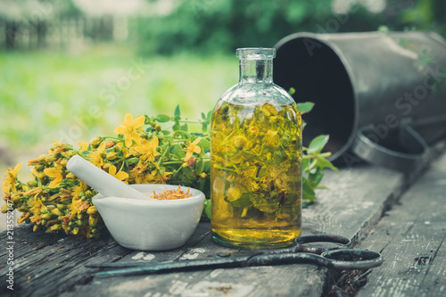 Hypericum - St Johns wort flowers, oil or infusion transparent bottle, mortar on wooden table Canvas Print