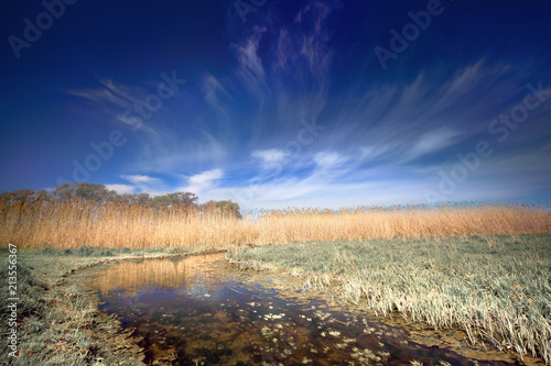 Authentic natural landscape, clouds in the sky touch the horizon, among the grass and reeds flowing small but wide creek.A beautiful view of the nature of the South of Russia in a tinted photo.