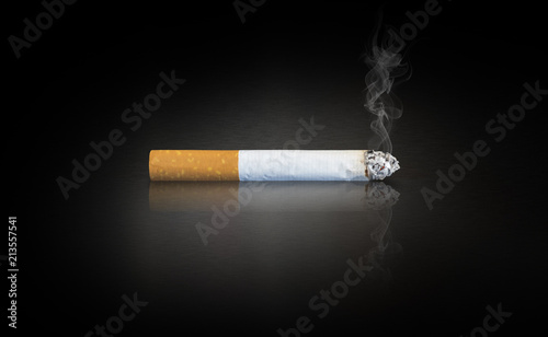 cigarette on a dark reflective surface Fototapet