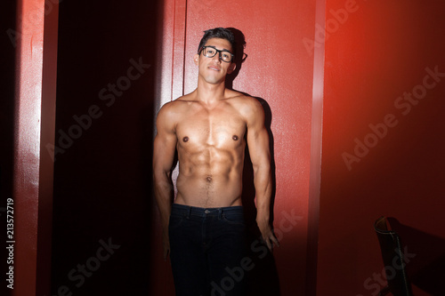 Fotomural Sexy nerdy guy leaning against wall