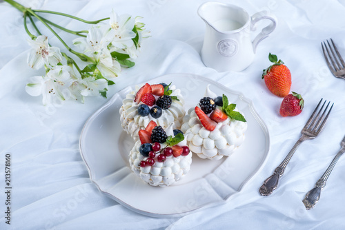 Foto op Aluminium Assortiment Delicate white meringues with fresh berries on the plate. Dessert Pavlova. Festive wedding cake.