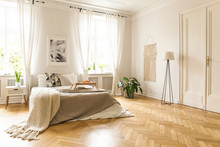 Blanket On Bed With Wooden Tray In Spacious Bright Bedroom Interior With Poster. Real Photo
