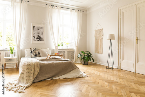 Fotografie, Obraz  Blanket on bed with wooden tray in spacious bright bedroom interior with poster