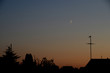 Conjunction between the crescent Moon and Venus seen in the evening in urban surroundings.