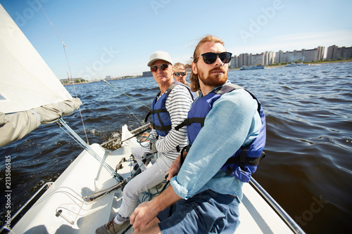 Tuinposter Zeilen Serious calm men in life jackets and sunglasses sitting in row on yacht and looking around during sailing tour on river
