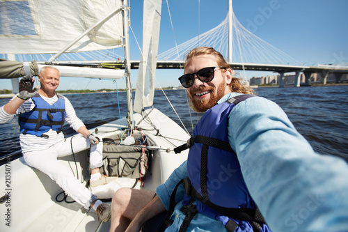 Fotomural  Cheerful handsome friends in blue life jackets taking selfie against beautiful b
