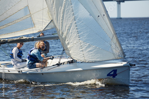 Cadres-photo bureau Voile Skilled handsome men participating in sailing competition: hipster young man handling sailboat using rope to direct mainsail on river