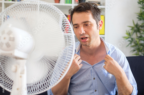 Man refreshing with electric fan against summer heat wave Canvas