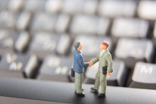 Business Deal Or Agreement And Success Concept. Two Miniature Businessmen Shaking Hands While Standing On The Keys Of A Black Keyboard.