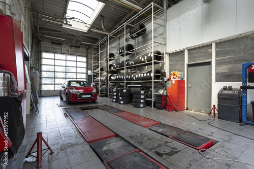 Fotografiet  Red car in a workshop with tires. Professional vehicle repair
