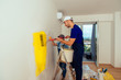 Young carefree couple painting wall in new house. Young family renovating their new apartment concept.