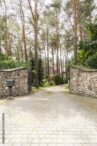 Foto  Stone gate and driveway into forest with residence. Real photo