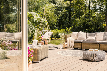 Fototapeta Pouf and rattan sofa on wooden patio with hanging chair in the garden. Real photo