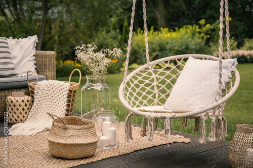 Fototapeta Pillow on hanging chair and basket on carpet in the garden during spring obraz