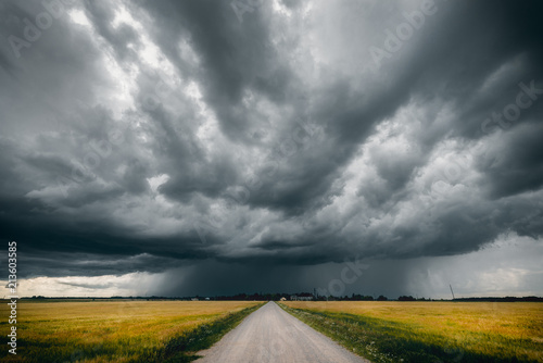 Poster Taupe Gravel road in the middle of green and yellow fields and stormy clouds above it
