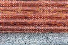 Retro Red Brick Wall And Cobblestone Pavement.