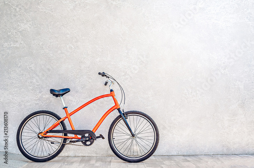 Orange color city bike against the wall with shiny silvery metallic plaster. Summertime concept