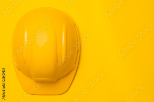 Fotografía  yellow construction helmet on a yellow background, head protection, concept, top