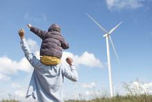 Happy Father And Son Playing At The Wind Turbines Generating Electricity. Having Quality Family Time Together.