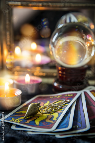 Tarot cards, crystal orb, pendulum, candellight  and a mirror, magic night scene