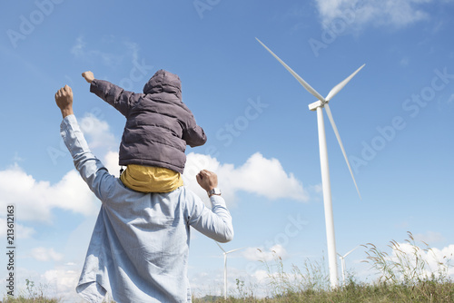 Fotografie, Obraz  happy father and son playing at the Wind turbines generating electricity