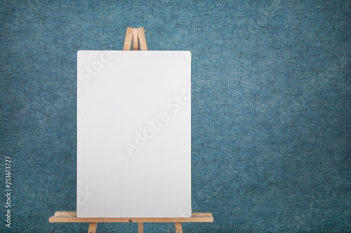 Photo  Wooden easel with blank canvas against a blue wall