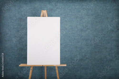 Wooden easel with blank canvas against a blue wall Wallpaper Mural
