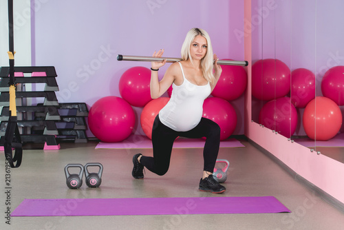 Carta da parati Beauty sporty pregnant woman working out in gym with balls on the background