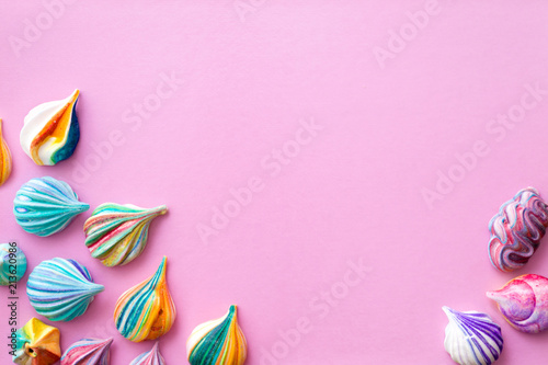Background of colorful meringue cakes on a pink basis. Appetizing meringues.