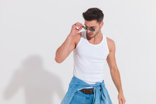Casual Man In Studio Light Fixes Sunglasses And Looks Down