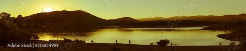 Fotobehang Zwavel geel Gente a contraluz en un Atardecer al lado de un Embalse o Lago al final del día de asueto