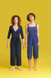 Indoor shot of two caucasian females in similar blue overalls posing at blank yellow studio wall. Funny teenage girl with ginger curly hairstyle standing near her smiling sister with short haircut