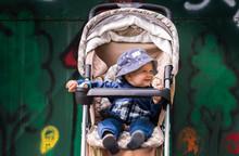 Baby Boy Sitting In The Strolling Stroller