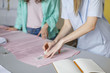 Close up fashion designers drawing with soap on pink textile in cozy sewing workshop